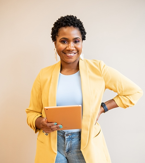 business-woman-smiling-with-yellow-blazer-holding-a-tablet